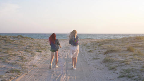Couple of young women walking sandy beach at the dusk Indie boho style Swimwear Footage