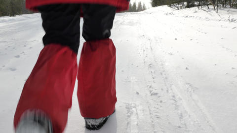 tourist in protective boots with big backpack walks on snow Stock Video Footage