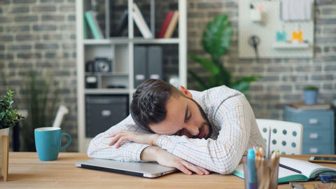 Tired businessman sleeping in workplace at desk with head on laptop computer Live Action