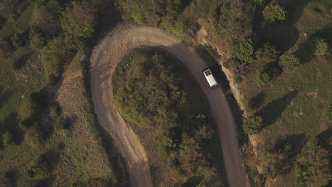 Top down view tourist vehicle traveling through wooded area at summer trip. Country sandy road makes Footage