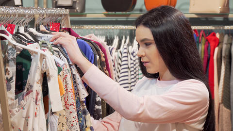 Woman looking shocked by the price of a dress at clothing store Live Action