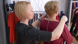 Mature woman trying necklace chain in accessories boutique. Seller helping to Footage