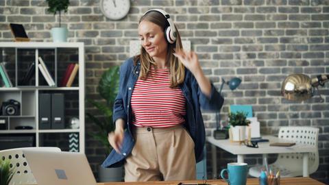 Cute girl having fun in office dancing listening to music in headphones resting Footage