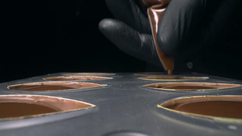 Chocolatier fills chocolate molds with liquid chocolate filling for praline Live Action