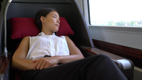 Woman relaxing sleeping in comfortable first class seat in train during travel Footage