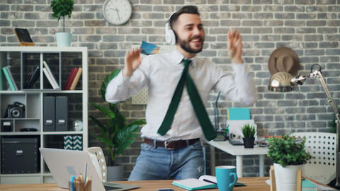Cheerful office worker listening to music in headphones dancing in workplace Live Action