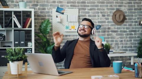 Happy guy in headphones listening to music at work having fun smiling Footage