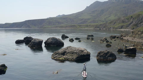 Beautiful picturesque sea bay with clean calm water. Large boulders lie in water near shore. Between Footage