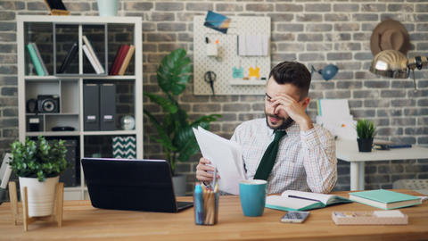 Unhappy office worker reading documents sighing thinking about trouble at work Footage