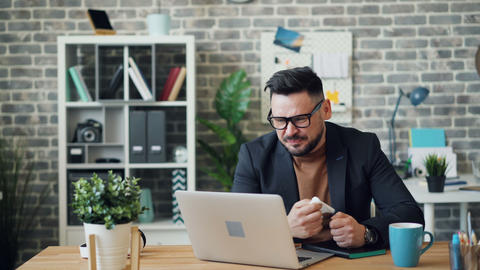 Sick young man using laptop in office then sneezing wiping nose with tissue Footage