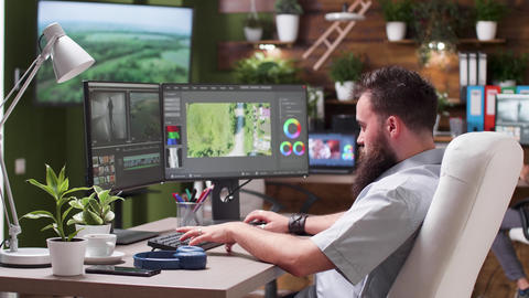 Professional video editor in busy creative agency puts headphones on Live Action