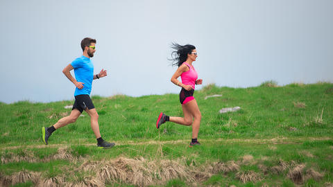 Personal trainer while training his sporty woman to run in the meadows1 Photo