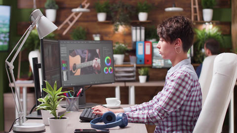 Female video editor and colorist puts her headphones on Live Action
