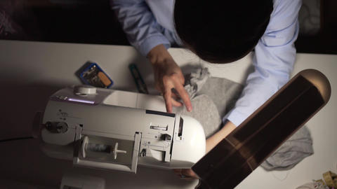 Woman's hands sewing with a sewing machine. Women's hands sew on a sewing Live Action