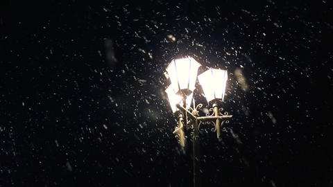 Street city lights illuminate the slowly falling snow. Night winter street lamp Live Action