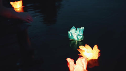 The girl launches a flashlight on the water. Glow lanterns on the water at night Footage