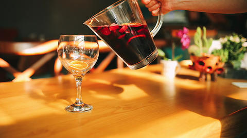 Woman hand pouring red wine cocktail from jug to glass. This alcoholic red wine cocktail is sangria Live Action