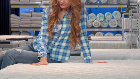 Red haired woman smiling, sitting on a new orthopedic mattress at the store Footage