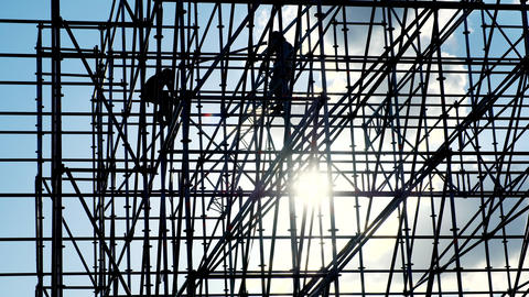 Workers at sunset builders assemble design. Silhouettes of men engineer worker Footage