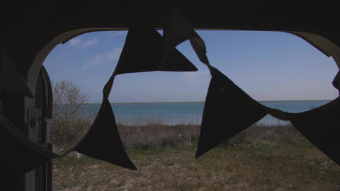 triangular flags swaying in the wind in the doorway of the trailer against the Footage
