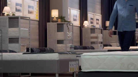 Male customer choosing orthopedic mattress and bed at furniture store Footage