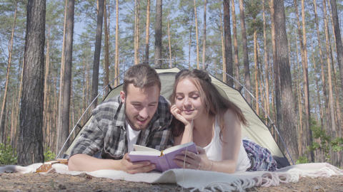 Portrait young man and pretty young woman lying near each other in the tent in Footage