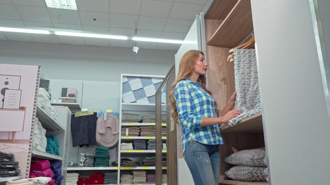 Beautiful woman smiling to the camera, buying a blanket at furnishings store Footage