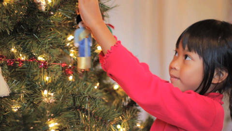 Cute Little Girl Hangs Asian Christmas Ornament Footage