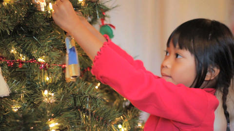 Cute Little Girl Hangs Asian Christmas Ornament Stock Video Footage
