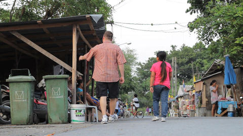 Asian Woman And Man Walk Through Slum Footage