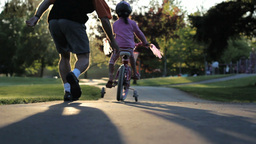 Excited Father Helps Daughter Ride Her New Bike Up Hill stock footage