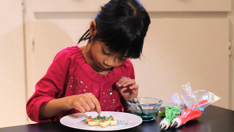 Excited Girl Adds Finishing Touch To Christmas Cookie Stock Video Footage