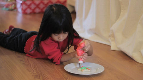 Girl Decorating Christmas Cookie With Red Icing Stock Video Footage
