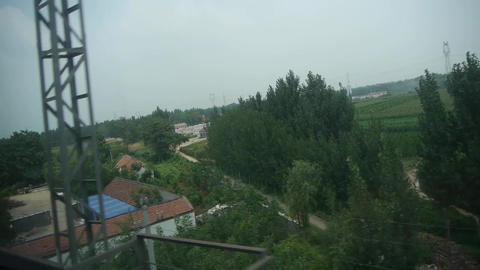 Villages plains tree crops farmland in rural countryside.Speeding train travel,s Footage
