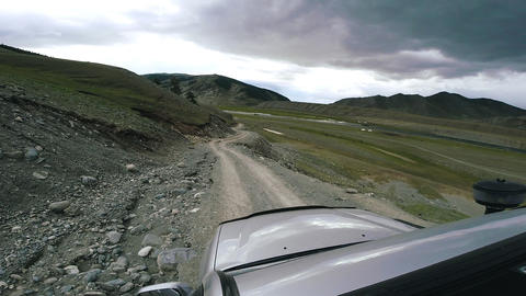 Car passing in high mountain road at summer. SUV rides a valley with mountains Live Action