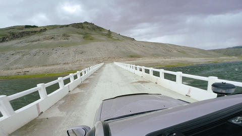 Auto travel: SUV rides on a high mountain road on white bridge over a river. POV Footage