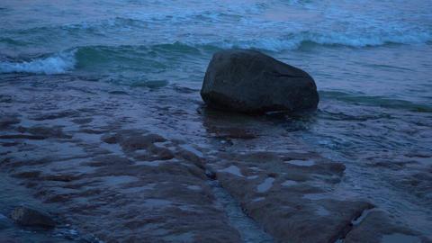 Dark shot rock in the ocean being hit by waves Stock Video Footage