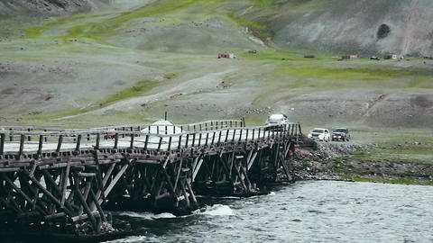 Auto travel: SUV rides on old wooden bridge on a high mountain road. Point of Footage
