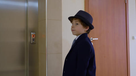 Child boy businessman is waiting elevator in his office. Adult's life parody Footage
