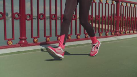 Fit female athlete running along urban bridge Footage