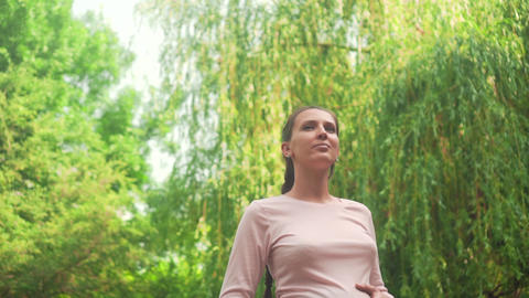 Pregnant girl in the park on background of green willow. Calm girl is standing Footage