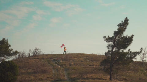 A man runs on a mountain with a canadian flag in his hand. The flag of Canada is Live Action