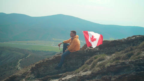 A young man in a yellow jacket, blue jeans and glasses sits on a ridge, followed Live Action