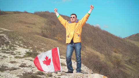 A man in a yellow jacket, blue jeans and glasses stands on a mountain, the flag Live Action
