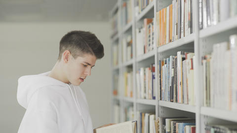 Man Looking For Book On Bookshelves At Library At College Footage