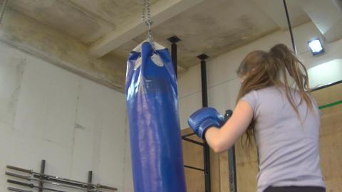 Slow Motion Kickboxing Woman Training Punching Bag In Fitness Studio GIF