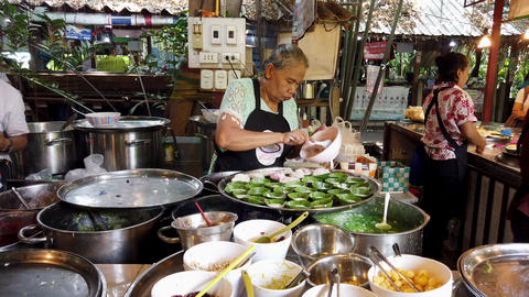 Bangkok, Thailand - 2019-03-17 - Woman Scoops Pudding Into Leaf Bowls at Market Footage