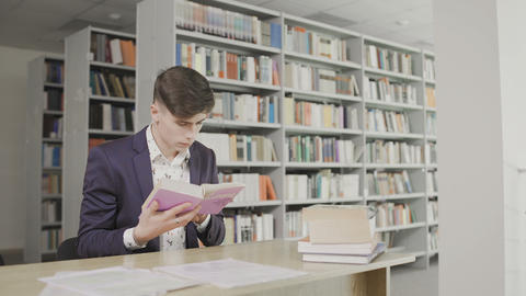 Young male student reading a book in a library. Man in a suit reading book on Live Action