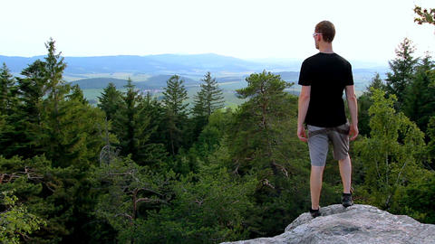 Young man looking to valley from rock, relax in landscape Footage