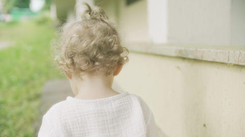Curly blonde baby girl walking, close-up shot from the back Footage